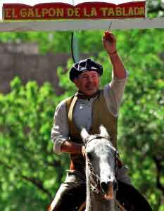 Destrezas Gauchescas: un grupo de gauchos a caballo compite a todo galope para ensartar con un puntero las sortijas que penden sobre sus cabezas