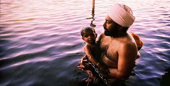 Un sij con su hijo en el Estanque del Néctar