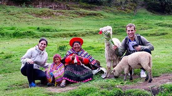 Testimonio de viaje a Perú de Laura y Víctor: foto con una mujer y su hija en la visita de la fuente para purificación durante el tour Cusco