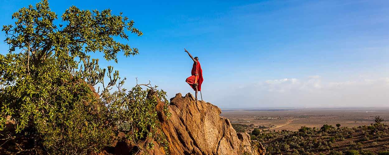 Un masai con Masai Mara de fondo - guía de turismo de Kenia